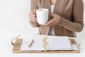 Woman drinking coffee with clipboard